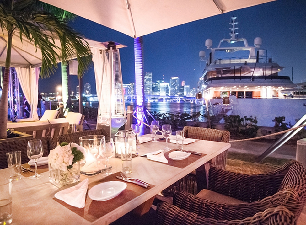 boat docked by a table at night in Miami at island gardens restaurant
